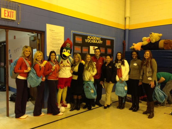 Fredbird and members of the St. Louis Cardinals front office staff prepare to distribute backpacks to kids at Oak Hill Elementary.