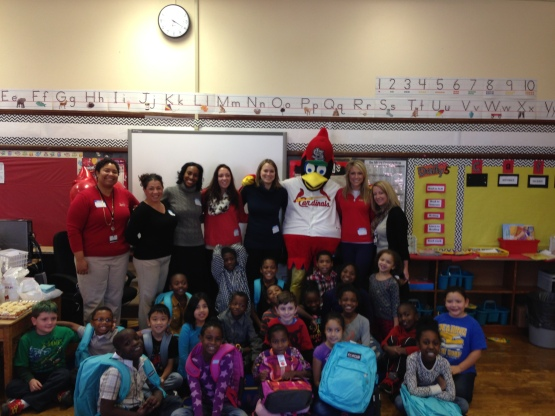 Fredbird and front office members pose with new backpacks delivered to children at Oak Hill Elementary