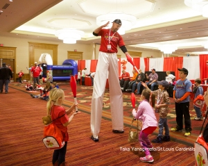 Stilt guy with little kids trying not to get crushed.